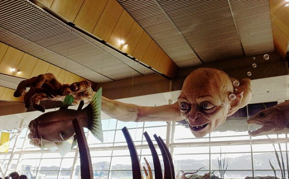 """""""Gollum with fishes sculpture, in Wellington Airport terminal"""" di According to Wellington Airport, the sculpture was created by a team of some 18 Weta Wetashop sculptors, painters, and other specialists, with art direction by Workshop Supervisor Rob Gillies.[1][2] Other sources credit the sculpture solely to Japanese artist Masayuki Ohashi.[3] I took this photo. - Opera propria (photo). Con licenza Public domain tramite Wikimedia Commons"""