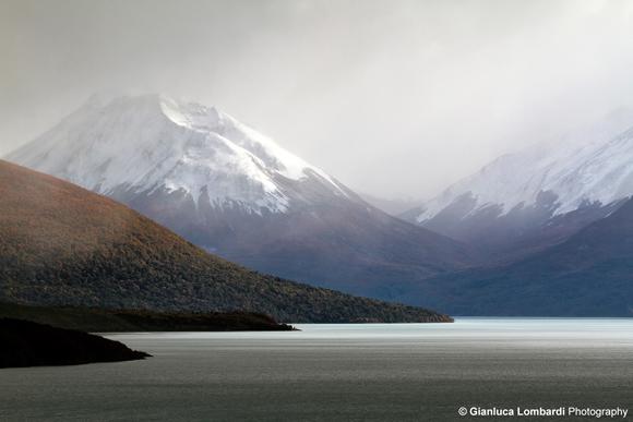 Nei pressi del Glaciar Perito Moreno, nella Provincia di Santa Cruz, Patagonia Argentina, timidi raggi del Sole attraversano la spessa coltre di nuvole sul Lago Argentino durante una forte nevicata, andando ad illuminare le pareti delle montagne della Cordigliera delle Ande e lo specchio d'acqua del lago. La luce sublime di questa scena è tutt'altro che rara nelle lande patagoniche.