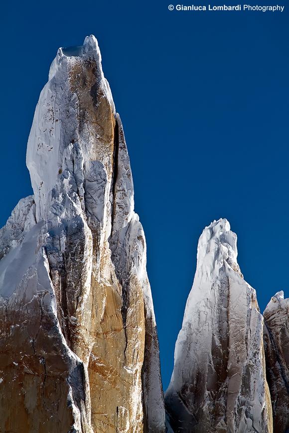 Dettaglio della cima del Cerro Torre coi suoi funghi di ghiaccio, accompagnata dalla cima minore di Aguja (guglia) Egger, di 2850 m.s.l.m., nel Parque Nacional Los Glaciares (Santa Cruz, Patagonia Argentina). Sublimati dall'aria gelida di Campo de Hielo Sur, i funghi di ghiaccio formatisi sulla sommità della montagna, cadono a valle da un momento all'altro. La vetta del Cerro Torre è considerata fra le più inaccessibili del Mondo perché, qualunque via si scelga, bisogna affrontare almeno 900 metri di parete granitica, per arrivare ad una cima perennemente ricoperta dai funghi di ghiaccio in continua genesi.