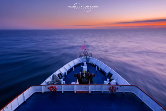 [20 Novembre 2015] Luci calde del cielo appena dopo il tramonto del Sole, mentre la Sea Adventurer attraversava la Convergenza Antartica su acque talmente placide da permettere di fermare il treppiedi e scattare una foto con esposizione di 4 secondi da sopra il ponte di comando, nella direzione di navigazione: Sud.