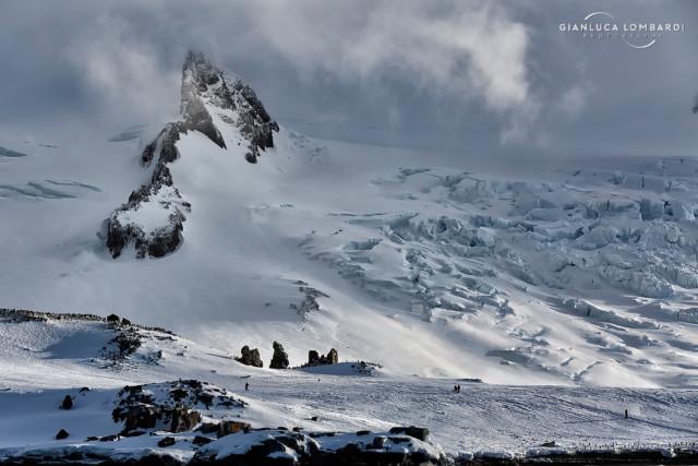 [21 Novembre 2015] Le insenature ancora ricoperte di neve di Half Moon Island e i ghiacciai di Livingston Island subito dietro. Nella foto si possono notare i membri della spedizione camminare su Half Moon Island.
